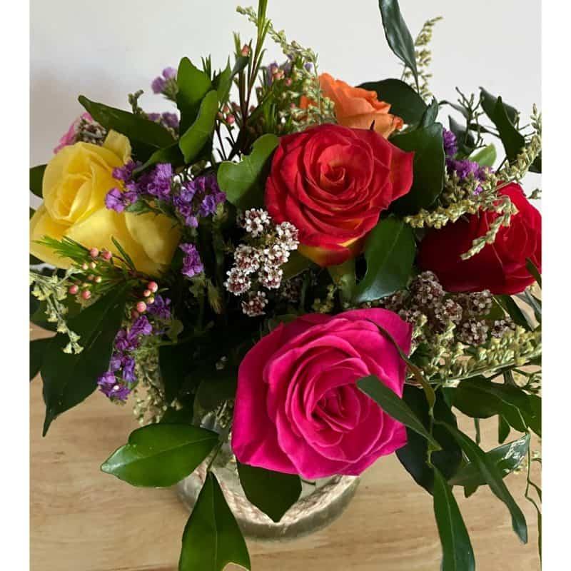 half dozen roses in glassware